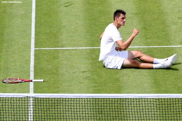 """""""Bernard Tomic celebrates after diving for a volley to win a point against James Blake at the All England Lawn and Tennis Club in London, England Thursday, June 27, 2013 during the 2013 Championships Wimbledon."""""""