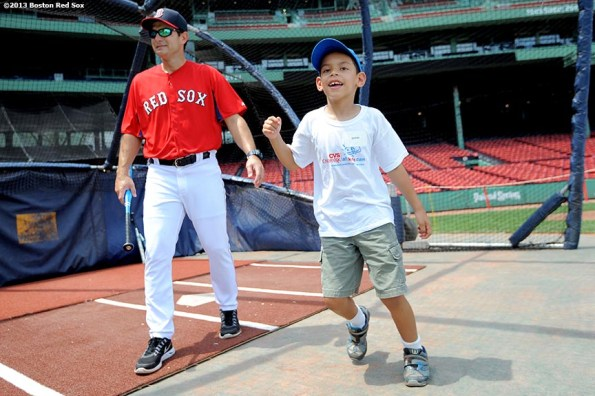 """""""Boston Red Sox hitting coach Greg Colbrunn exits the batting cage as a CVS Hitting Clinic participant celebrates after taking batting practice at Fenway Park in Boston, Massachusetts Monday, July 22, 2013."""""""