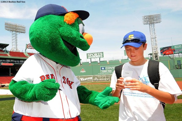"""""""Boston Red Sox mascot Wally the Green Monster signs an autograph for a CVS Hitting Clinic participant after taking batting practice on the field at Fenway Park in Boston, Massachusetts Monday, July 22, 2013."""""""