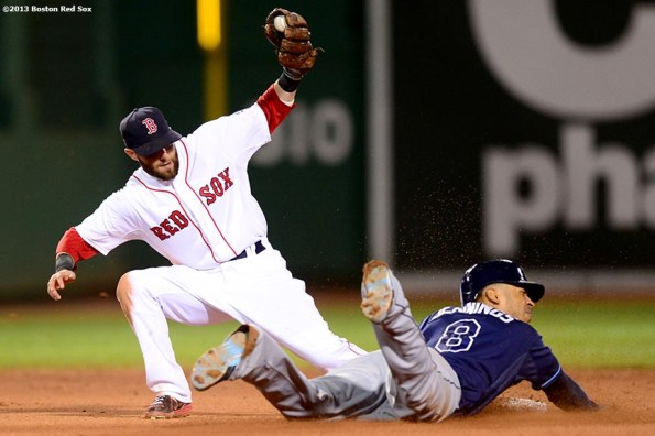"""""""Boston Red Sox second baseman Dustin Pedroia applies a tag on center fielder Desmond Jennings during the seventh inning of a game against the Tampa Bay Rays Thursday, July 24, 2013 at Fenway Park in Boston, Massachusetts."""""""