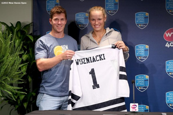 """""""Caroline Wozniacki is presented with a Yale University Hockey jersey as a parting gift after losing to Simona Halep in the semi-finals on Day 8 of the New Haven Open at Yale University in New Haven, Connecticut Friday, August 20, 2013."""""""