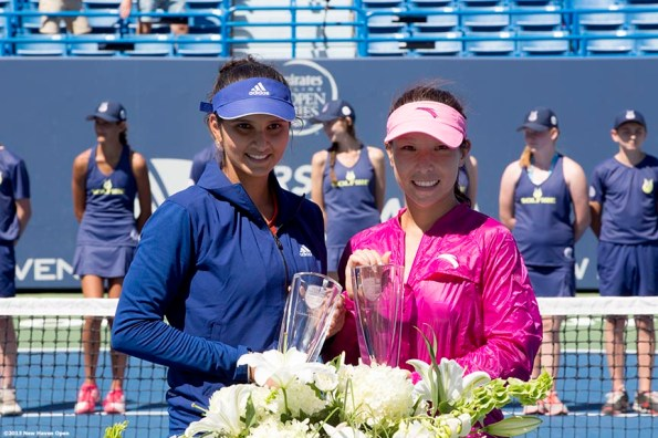 """""""Sania Mirza and Jie Zheng pose with the trophies after winning the doubles title at the New Haven Open at Yale University in New Haven, Connecticut Saturday, August 24, 2013."""""""