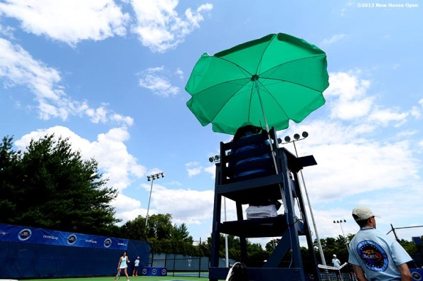 """""""A chair umpire sits under an umbrella on Day 1 of the New Haven Open at Yale University in New Haven, Connecticut Friday, August 16, 2013."""""""