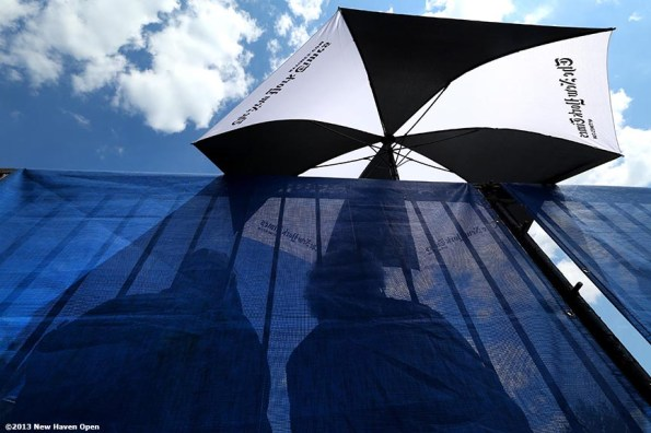 """""""Fans sit under an umbrella as they watch a match on Day 2 of the New Haven Open at Yale University in New Haven, Connecticut Saturday, August 17, 2013."""""""