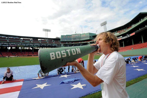 """""""John Coyne, US Flag Coordinator of the Boston Red Sox, gives instructions as members of the Red Sox Front Office help roll an American Flag in preparation for a 9/11 memorial flag drop over the Green Monster Friday, September 13, 2013 at Fenway Park in Boston, Massachusetts."""""""
