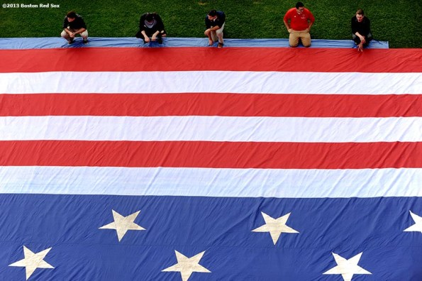 """""""Members of the Boston Red Sox Front Office help roll an American Flag in preparation for a 9/11 memorial flag drop over the Green Monster Friday, September 13, 2013 at Fenway Park in Boston, Massachusetts."""""""