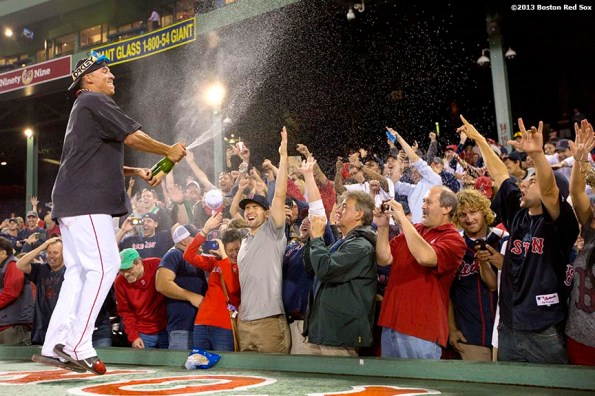 """""""Boston Red Sox outfielder Quintin Berry sprays fans with champagne on top of the dugout during an on-field celebration after the Red Sox clinched the American League East title with a 6-3 win over the Toronto Blue Jays Friday, September 20, 2013 at Fenway Park."""""""