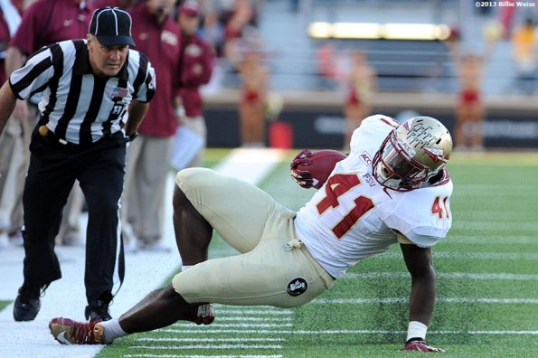"""""""Florida State Seminoles fullback Chad Abram slips along the sideline after a carry during the third quarter of a game against the Boston College Eagles at Alumni Stadium in Chestnut Hill, Massachusetts Saturday, September 28, 2013."""""""