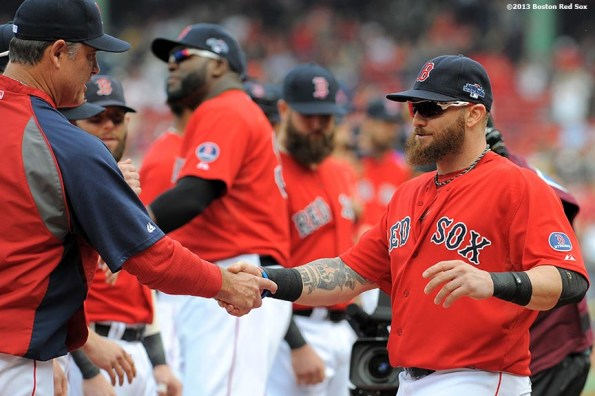 """""""Boston Red Sox outfielder Jonny Gomes high fives teammates during a pre-game ceremony before the first game of the American League Division Series between the Boston Red Sox and the Tampa Bay Rays Friday, October 4, 2013 at Fenway Park in Boston, Massachusetts."""""""