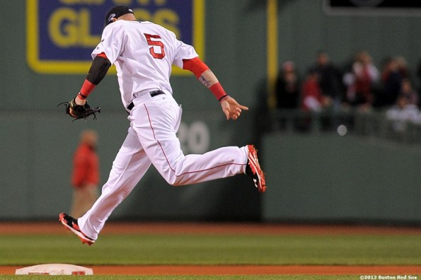 """""""Boston Red Sox left fielder Jonny Gomes hops over second base during the first inning of game two of the American League Championship Series against the Detroit Tigers Sunday, October 13, 2013 at Fenway Park in Boston, Massachusetts."""""""