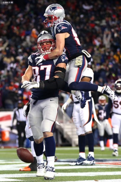 """""""New England Patriots wide receiver Danny Amendola jumps on tight end Rob Gronkowski after Gronkowski caught a touchdown pass during a game against the Denver Broncos Sunday, November 24, 2013 at Gillette Stadium in Foxborough, Massachusetts."""""""