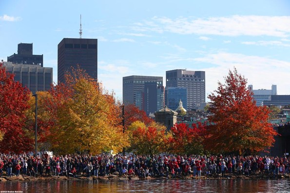 """""""Fans gathered along the banks of the Charles River cheer during the Rolling Rally World Series Championship Parade through downtown Boston, Massachusetts Saturday, November 2, 2013."""""""