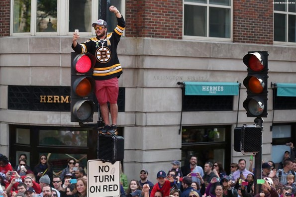 """""""A fan cheers atop a street light along Boylston Street during the Rolling Rally World Series Championship Parade through downtown Boston, Massachusetts Saturday, November 2, 2013."""""""