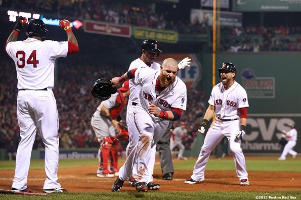 """""""Boston Red Sox left fielder Jonny Gomes celebrates alongside designated hitter David Ortiz, third baseman Xander Bogaerts, and center fielder Jacoby Ellsbury after scoring on an RBI double by right fielder Shane Victorino during the third inning of game six of the 2013 World Series against the St. Louis Cardinals Wednesday, October 30, 2013 at Fenway Park in Boston, Massachusetts."""""""