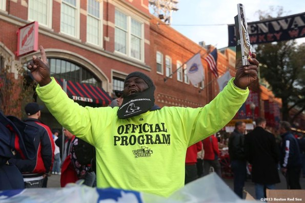 """""""A vendor sells programs on Yawkey Way before game six of the 2013 World Series between the Boston Red Sox and the St. Louis Cardinals Wednesday, October 30, 2013 at Fenway Park in Boston, Massachusetts."""""""