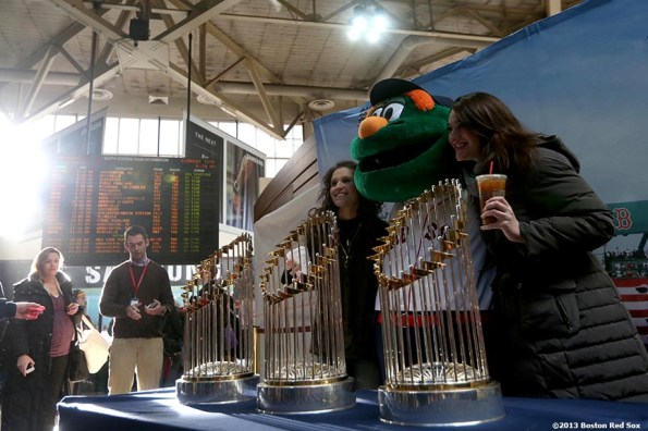 """""""Fans pose with Boston Red Sox mascot Wally the Green Monster and the 2004, 2007, and 2013 World Series trophies at South Station in Boston, Massachusetts Thursday, December 12, 2013 as part of the Red Sox Holiday Caravan to various locations throughout Boston."""""""
