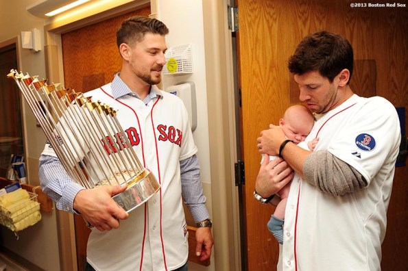 """""""Boston Red Sox pitcher Craig Breslow holds a baby as catcher Ryan Lavarnway holds the World Series trophy during a visit to Beth Israel Deaconess Medical Center in Boston, Massachusetts Friday, December 13, 2013 as part of the Red Sox Holiday Caravan to various locations throughout Boston."""""""