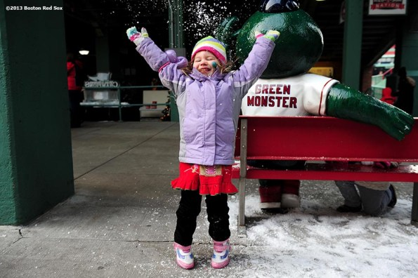 """""""Sienna Kaplan, 4, of Melrose, MA plays with snow during the annual Christmas at Fenway celebration Saturday, December 14, 2013, which featured speaking appearances and autograph sessions with players and coaches, holiday themed attractions and decorations, and opportunities for fans to purchase tickets for the 2014 season."""""""