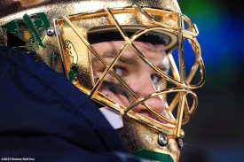 """""""A member of the Notre Dame hockey team looks on from the bench during a game against Boston College at Frozen Fenway 2014 Saturday, January 4, 2014 at Fenway Park in Boston, Massachusetts."""""""