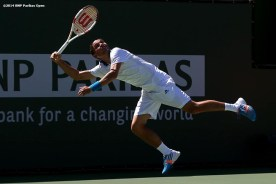 """""""Alexandr Dolgopolov jumps as he returns a shot from Fabio Fognini in a fourth round match at the 2014 BNP Paribas Open Wednesday, March 12, 2014 in Indian Wells, California."""""""