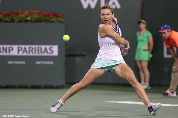 """Simona Halep returns a shot from Agnieszka Radwanska in the semifinal of the 2014 BNP Paribas Open Friday, March 14, 2014 in Indian Wells, California."""