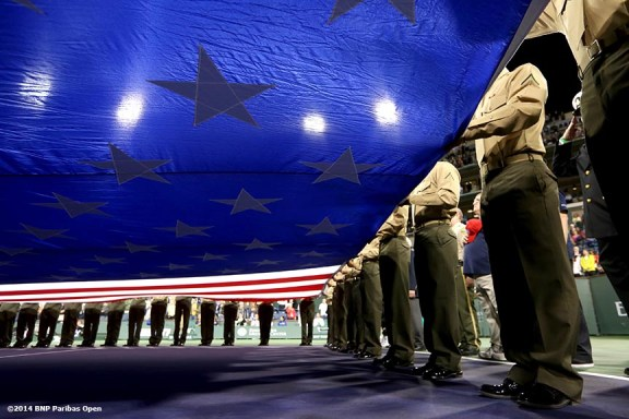 """""""Military members hold an American Flag during a 'Salute To Heroes' ceremony at the Indian Wells Tennis Garden in Indian Wells, California Friday, March 7, 2014."""""""