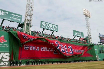 """""""The 2013 World Series championship banner is dropped over the Green Monster during the Boston Red Sox World Series ring ceremony at the 2014 season home opener Friday, April 4, 2014 at Fenway Park in Boston, Massachusetts."""""""
