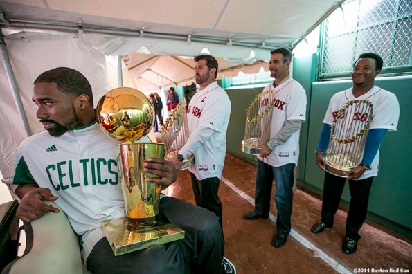 """""""Former Boston Celtics player Leon Powe and former Boston Red Sox players Jason Varitek, Mike Lowell, and Pedro Martinez hold championship trophies before they are introduced during the Boston Red Sox World Series ring ceremony at the 2014 season home opener Friday, April 4, 2014 at Fenway Park in Boston, Massachusetts."""""""