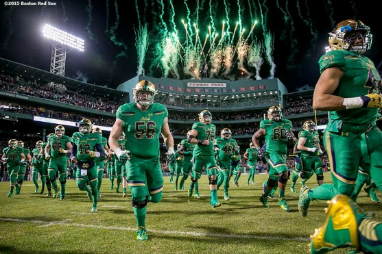 """""""Fireworks explode as members of Notre Dame run onto the field during the Shamrock Series Football at Fenway game against Boston College at Fenway Park in Boston, Massachusetts Saturday, November 21, 2015."""""""
