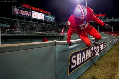 """""""A member of Catholic Memorial High School jumps over the bullpen wall before a high school football game against Boston College High School at Fenway Park in Boston, Massachusetts Wednesday, November 25, 2015."""""""