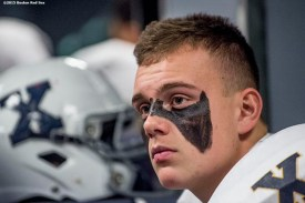 """""""A members of the Xaverian Brothers High School football team looks on in the locker room before a game against St. John's Preparatory School at Fenway Park in Boston, Massachusetts Wednesday, November 25, 2015."""""""
