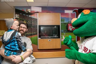 """""""Boston Red Sox mascot Wally the Green Monster greets a patient at Massachusetts General Hospital during the Holiday Caravan in Boston, Massachusetts Friday, December 10, 2015."""""""