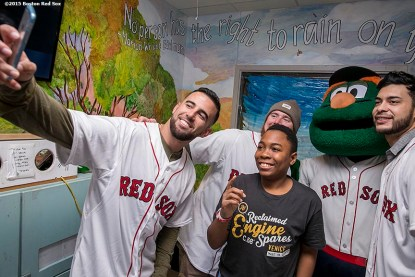 """""""Boston Red Sox infielder Deven Marrero, pitcher Robbie Ross Jr. and Noe Ramirez, and mascot Wally the Green Monster pose for a selfie photograph with a patient at Boston Medical Center during the Holiday Caravan in Boston, Massachusetts Friday, December 10, 2015."""""""