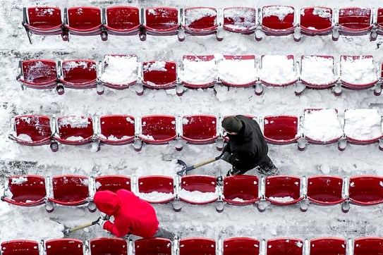 """""""Workers shovel snow from the seats in preparation for the Big Air at Fenway ski and snowboard competition at Fenway Park in Boston, Massachusetts Monday, January 25, 2016."""""""