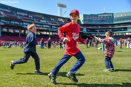 """""""Fans play in the outfield during Little League Opening Day at Fenway Park in Boston, Massachusetts Saturday, April 9, 2016."""""""