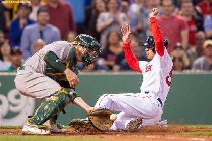 BOSTON, MA - MAY 10: Mookie Betts #50 of the Boston Red Sox slides as he avoids the tag of Steven Vogt # 21 of the Oakland Athletics to score during the third inning of a game against the Oakland Athletics on May 10, 2016 at Fenway Park in Boston, Massachusetts. (Photo by Billie Weiss/Boston Red Sox/Getty Images) *** Local Caption *** Mookie Betts; Steven Vogt