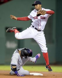 BOSTON, MA - MAY 24: Xander Bogaerts #2 of the Boston Red Sox turns a double play as Carlos Gonzalez #5 of the Colorado Rockies slides during the fourth inning of a game on May 24, 2016 at Fenway Park in Boston, Massachusetts. (Photo by Billie Weiss/Boston Red Sox/Getty Images) *** Local Caption *** Xander Bogaerts; Carlos Gonzalez
