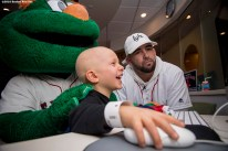 """""""Boston Red Sox infielder Deven Marrero and mascot Wally the Green Monster play computer games with a patient during a visit to The Jimmy Fund at Dana-Farber Cancer Institute as part of the 2016 Holiday Caravan in Boston, Massachusetts Friday, December 9, 2016."""""""