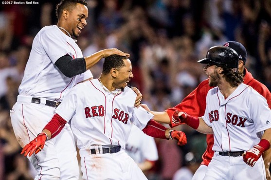 BOSTON, MA - AUGUST 16: Mookie Betts #50 of the Boston Red Sox is mobbed by teammates after hitting the game winning walk-off double during the ninth inning of a game against the St. Louis Cardinals on August 16, 2017 at Fenway Park in Boston, Massachusetts. (Photo by Billie Weiss/Boston Red Sox/Getty Images) *** Local Caption *** Mookie Betts