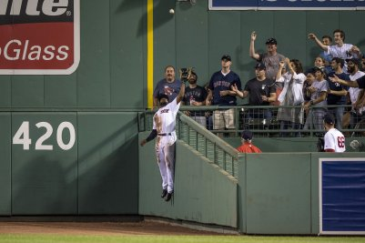 """""""Jackie Bradley Jr. #19 of the Boston Red Sox leaps over the wall to rob a home run ball hit by Aaron Judge #99 of the New York Yankees during the eighth inning of a game on July 16, 2017 at Fenway Park in Boston, Massachusetts."""