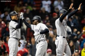 BOSTON, MA - APRIL 12: Didi Gregorius #18 high fives Giancarlo Stanton #27 and Aaron Judge #99 of the New York Yankees after scoring during the ninth inning of a game against the Boston Red Sox on April 12, 2018 at Fenway Park in Boston, Massachusetts. (Photo by Billie Weiss/Boston Red Sox/Getty Images) *** Local Caption *** Aaron Judge; Giancarlo Stanton; Didi Gregorius