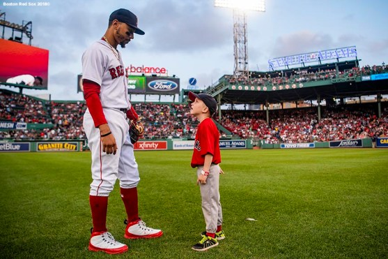 BOSTON, MA - AUGUST 21: Mookie Betts #50 of the Boston Red Sox takes the field with a Jimmy Fund patient before a game against the Cleveland Indians on August 21, 2018 at Fenway Park in Boston, Massachusetts. (Photo by Billie Weiss/Boston Red Sox/Getty Images) *** Local Caption *** Mookie Betts