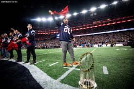 FOXBOROUGH, MA - NOVEMBER 4: Manager Alex Cora of the Boston Red Sox reveals a New England Patriots jersey alongside the World Series trophy before a game between the New England Patriots and the Green Bay Packers on November 4, 2018 at Gillette Stadium in Foxborough, Massachusetts. (Photo by Billie Weiss/Boston Red Sox/Getty Images) *** Local Caption *** Alex Cora