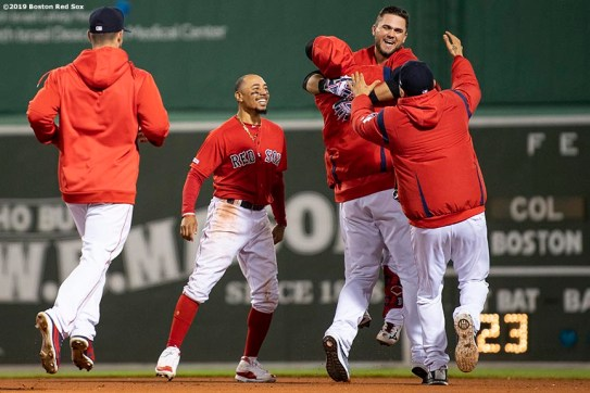 BOSTON, MA - MAY 15: Michael Chavis #23 of the Boston Red Sox reacts with Mookie Betts #50 and teammates after hitting a game winning walk-off RBI single during the tenth inning of a game against the Colorado Rockies on May 15, 2019 at Fenway Park in Boston, Massachusetts. (Photo by Billie Weiss/Boston Red Sox/Getty Images) *** Local Caption *** Michael Chavis; Mookie Betts