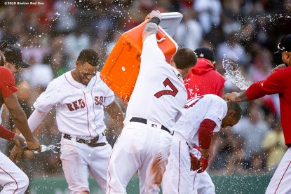 BOSTON, MA - JUNE 12: Mookie Betts #50 of the Boston Red Sox is doused with water by teammates after being walked to force in the game winning run on a walk off during the ninth inning of a game against the Texas Rangers on June 12, 2019 at Fenway Park in Boston, Massachusetts. (Photo by Billie Weiss/Boston Red Sox/Getty Images) *** Local Caption *** Mookie Betts