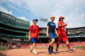 BOSTON, MA - AUGUST 22: Fans roam the warning track before the continuation of a game between Boston Red Sox and the Kansas City Royals on August 22, 2019 at Fenway Park in Boston, Massachusetts. The original game was suspended due to weather on August 7 in the top of the 10th inning with a tied score of 4-4. (Photo by Billie Weiss/Boston Red Sox/Getty Images) *** Local Caption ***