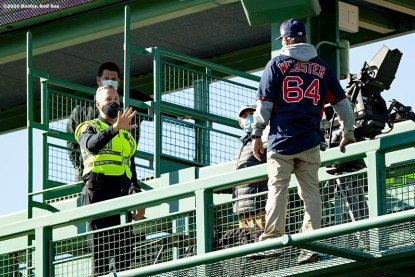 BOSTON, MA - SEPTEMBER 20: A member of the police escorts a fan who broke into the stadium and interfered with the game while climbing on the center field camera platform during the eighth inning of a game between the Boston Red Sox and the New York Yankees on September 20, 2020 at Fenway Park in Boston, Massachusetts. The 2020 season had been postponed since March due to the COVID-19 pandemic. (Photo by Billie Weiss/Boston Red Sox/Getty Images) *** Local Caption ***