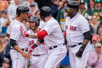 """Boston Red Sox left fielder Jonny Gomes celebrates with shortstop Xander Bogaerts, second baseman Dustin Pedroia, and designated hitter David Ortiz after hitting a grand slam home run during the first inning of a game against the Oakland Athletics Saturday, May 4, 2014 at Fenway Park in Boston, Massachusetts."""