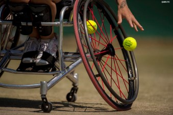 """Jordanne Whiley bounces a tennis ball alongside partner Yui Kamiji during a ladies' wheelchair doubles match against Katharina Kruger and Sharon Walraven at the All England Lawn and Tennis Club in London, England Friday, July 4, 2014 during the 2014 Championships Wimbledon."""