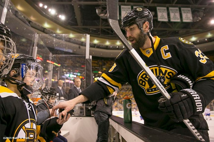 """Make-A-Wish recipient Jimmy Bjorkman of West Salem, Wisconsin receives a puck from Boston Bruins player Zdeno Chára as he watches warm ups from the bench before a hockey game between the Boston Bruins and the Montreal Canadiens at TD Garden in Boston, Massachusetts Sunday, February 8, 2015."""